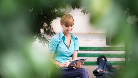 Portrait of happy young female college student typing on digital tablet computer and sitting on bench in city park